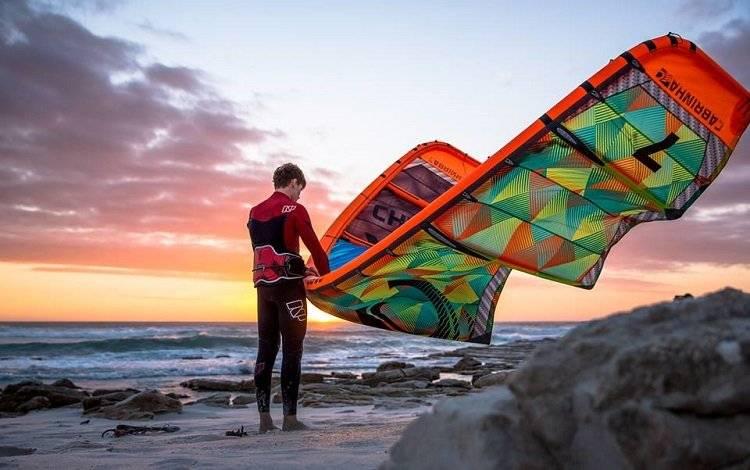 man cheks his kite before launch