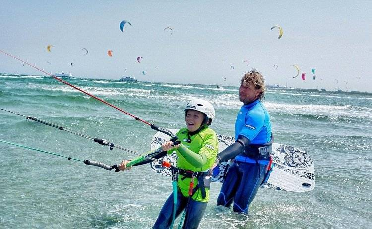 kid launches kite with help from a instructor