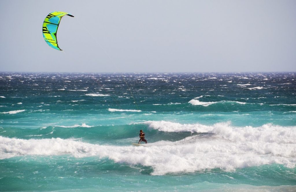 A man kitesurf in the ocean with naish kite